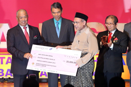 Deputy Prime Minister Tan Sri Muhyiddin Yassin (left) presenting a mock cheque to 2014 science and technology novelist winner Mat Rofa Ismail during the launch of the national-level National Language Month at PICC. (source:www.nst.com.my)